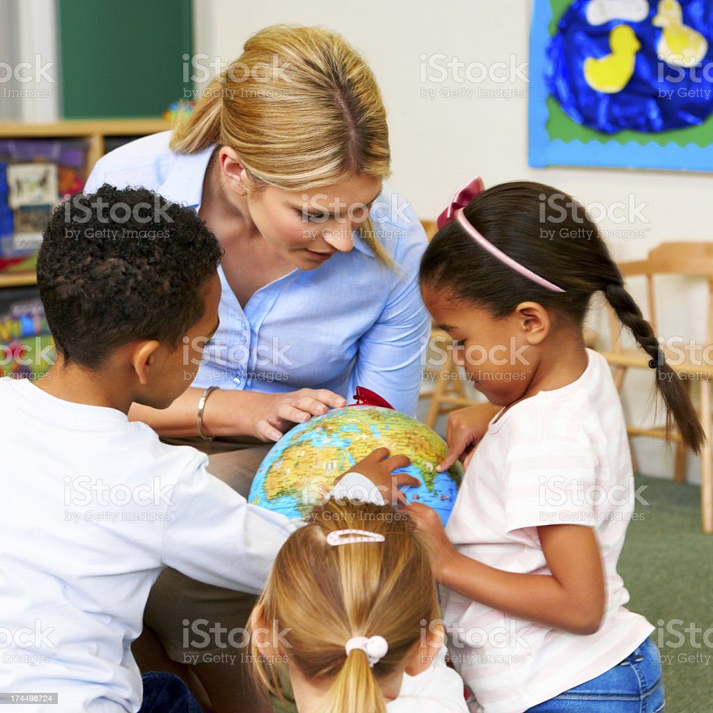 Preschool teacher explaining the world to children royalty-free stock photo