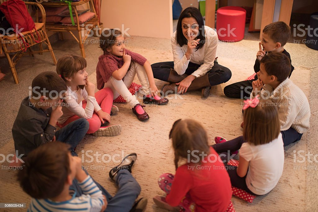 Preschool teacher playing leisure games with group of children. stock photo