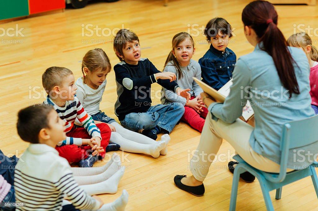 Preschool teacher reading a book to children in classroom. stock photo