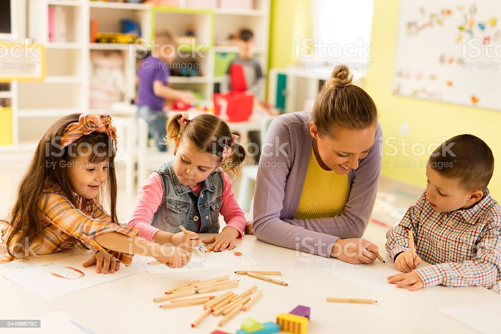 Preschool teacher sketching with kids during art class at kindergarten. stock photo
