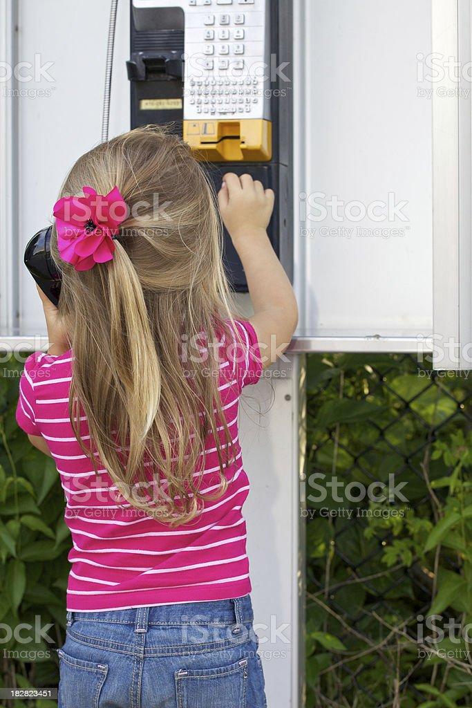 preschooler calling on a public phone royalty-free stock photo