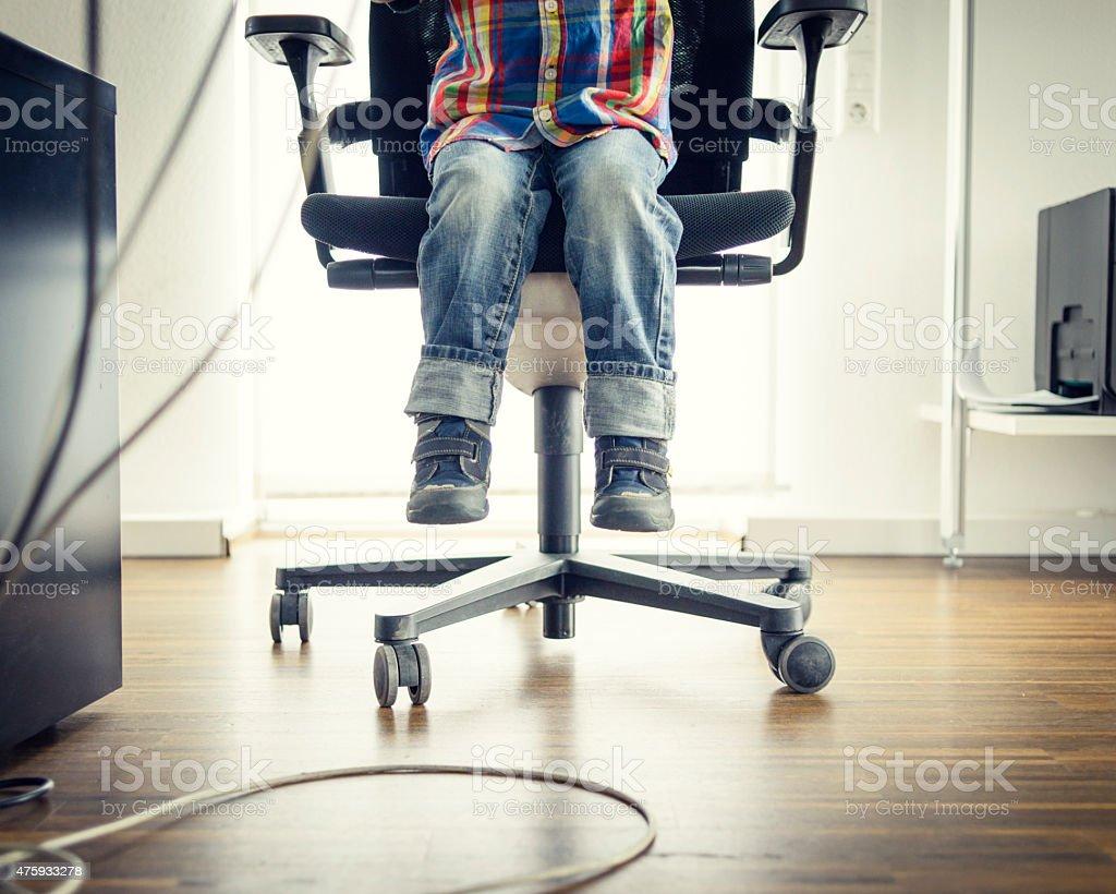 Preschooler Sitting at Grown-ups Office Desk, View of Feet stock photo