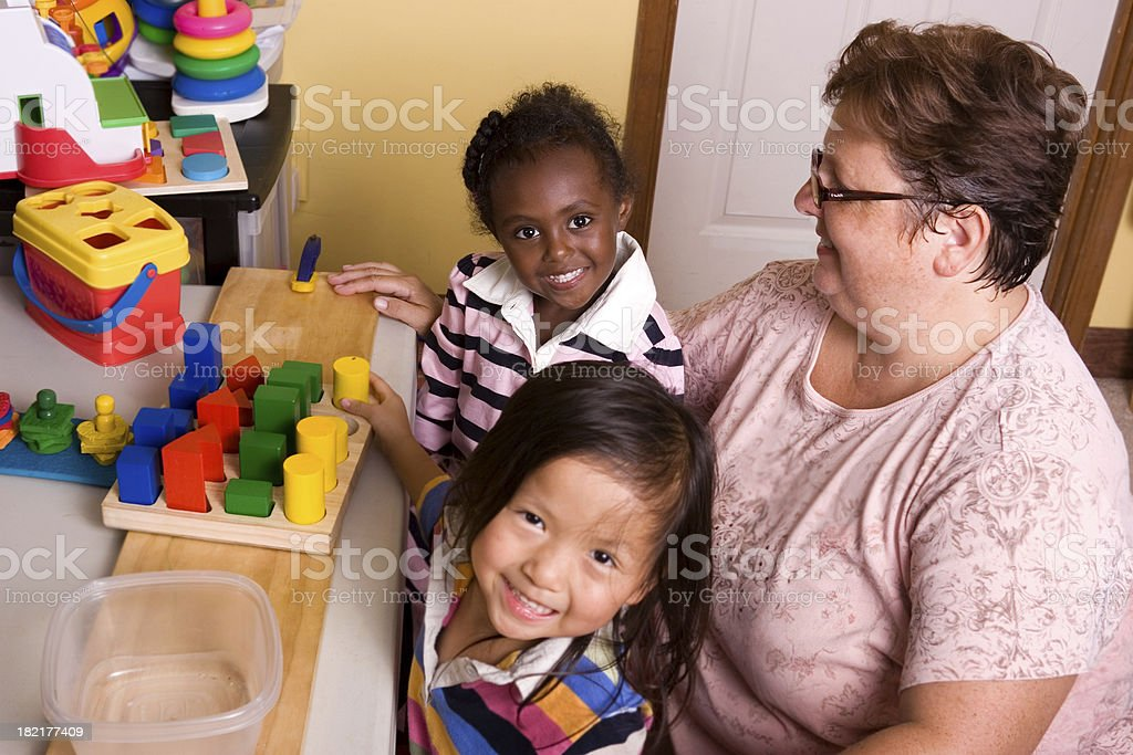 Preschoolers playing with teacher royalty-free stock photo