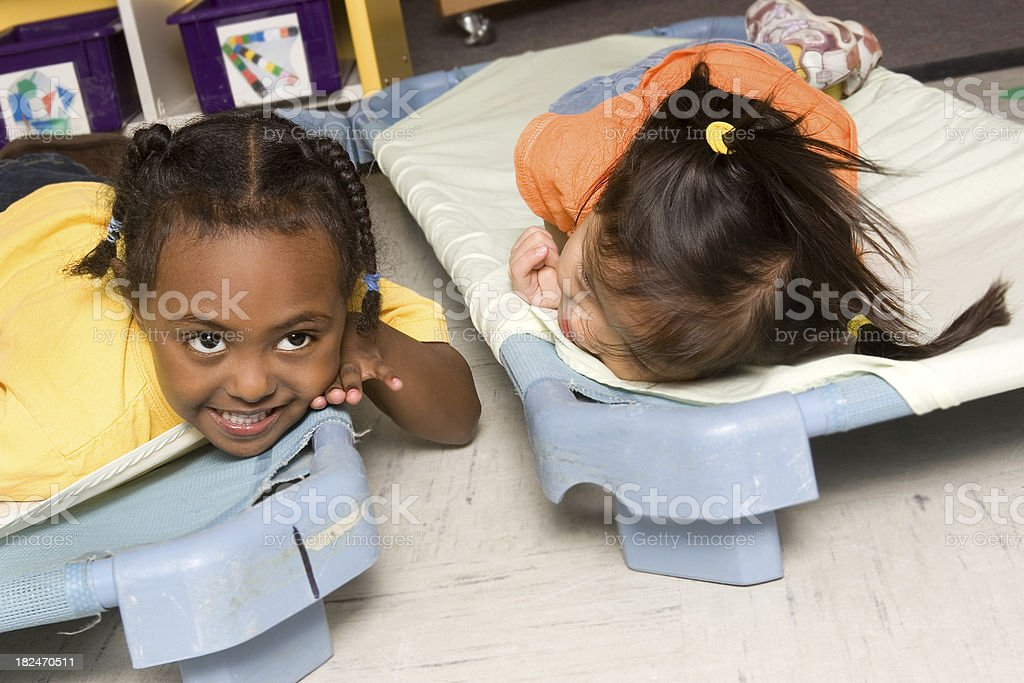 Preschoolers whispering during naptime stock photo