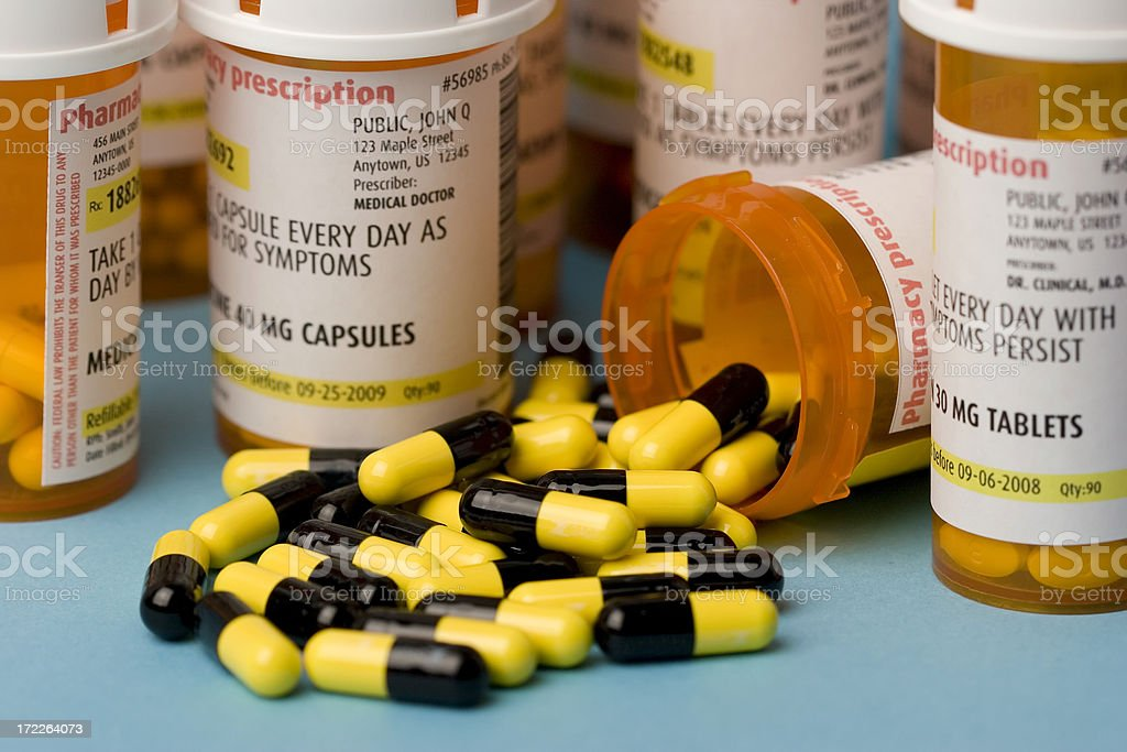 Prescription bottle with pills spilled out stock photo