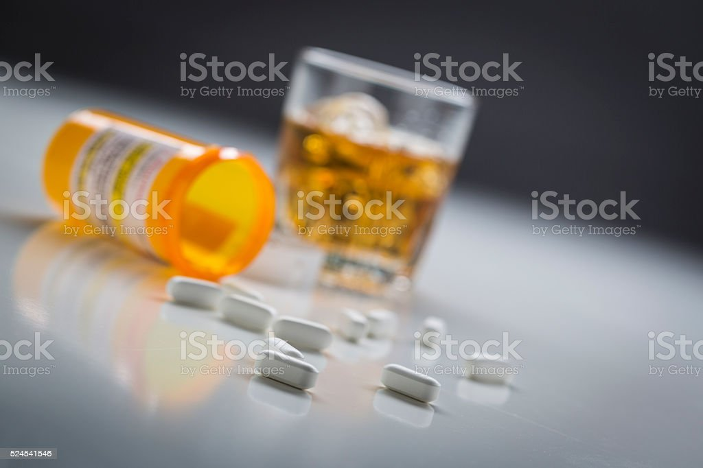 Prescription Drugs Spilled From Fallen Bottle Near Glass of Alcohol stock photo