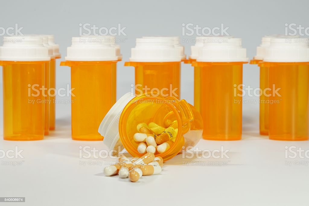 Prescription Medicine Bottles and Capsules With Grey Background stock photo