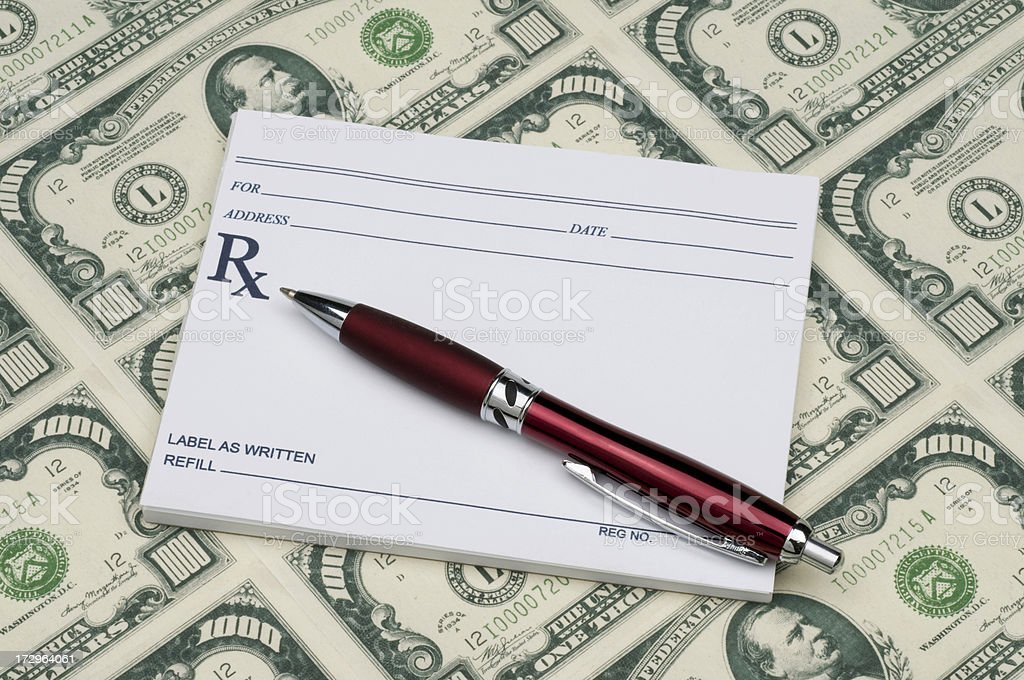 Prescription pad w/pen on top of thousand dollar bills-costly perscriptions stock photo