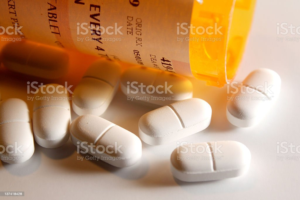 Prescription pain pills tumble from container. stock photo