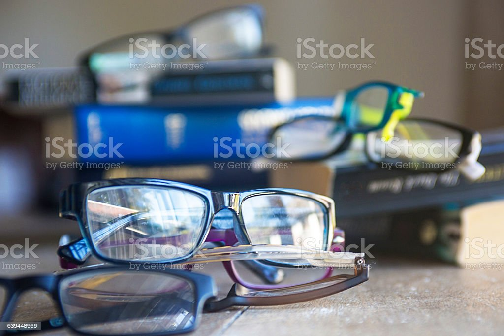 Prescription  reading glasses with books in the background stock photo