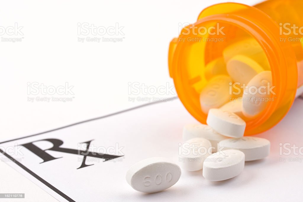 Prescription tablets spilling from an orange container stock photo