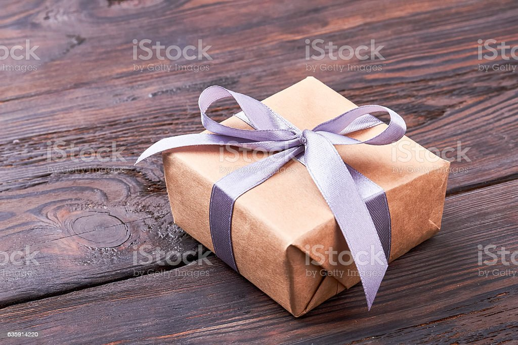 Present box on wooden surface. stock photo