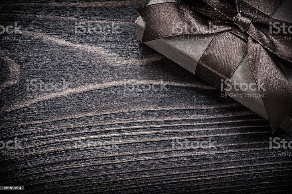 Present box with brown ribbon on wooden board holidays concept stock photo