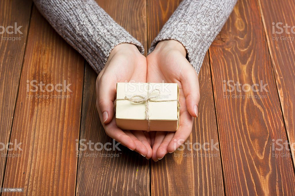 Present,  gift. Close up of female hands holding small gift stock photo