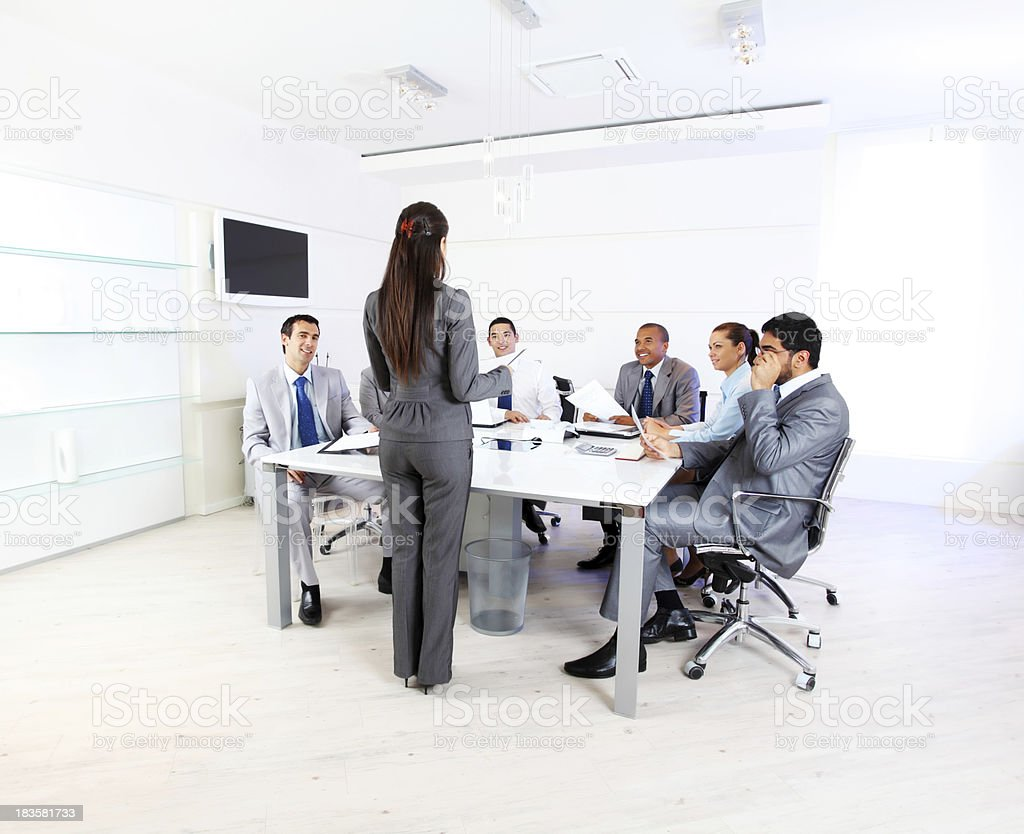 Presentation of a  young business woman, team listening her. royalty-free stock photo