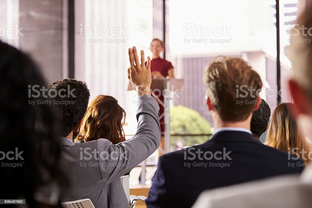 Presenter at business seminar takes a question from audience stock photo