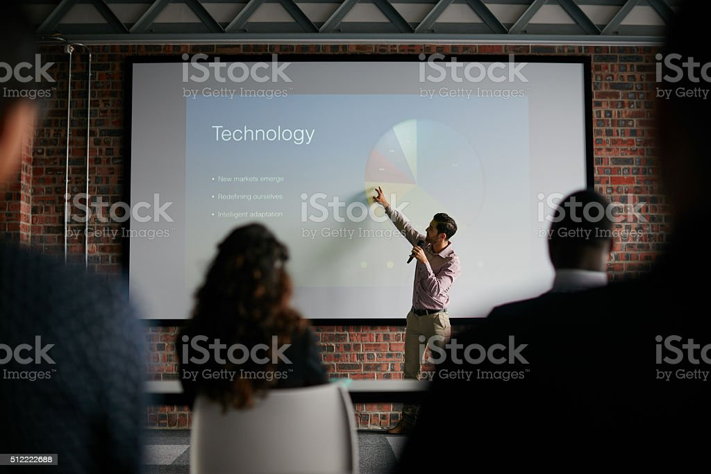 Presenting key notes to his colleagues stock photo