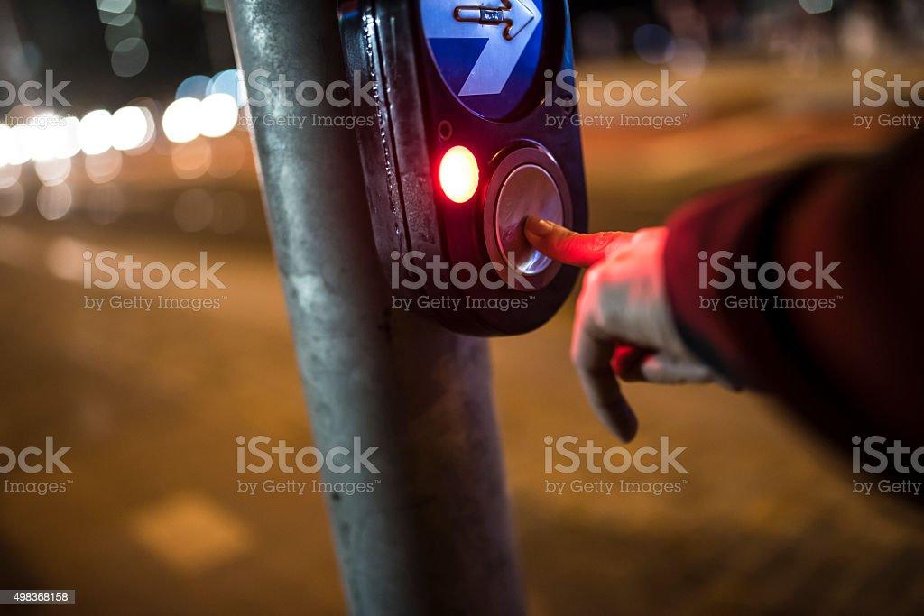 Pressing button at crosswalk stock photo
