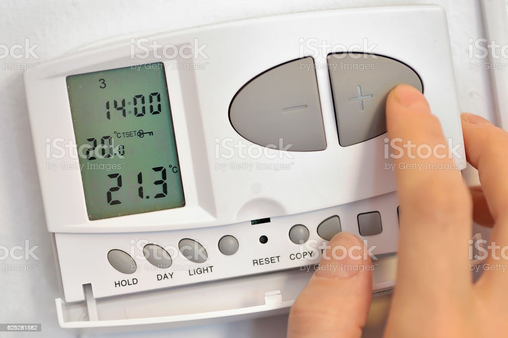 pressing button on digital thermostat stock photo