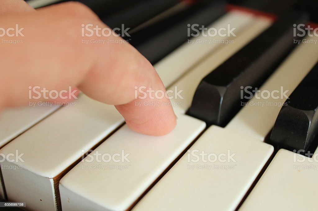 Pressing key of piano stock photo