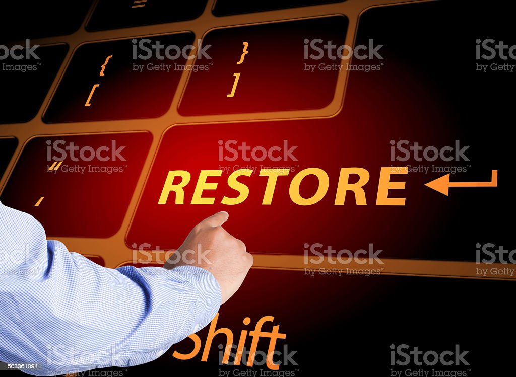 Hand pressing restore button on keyboard stock photo