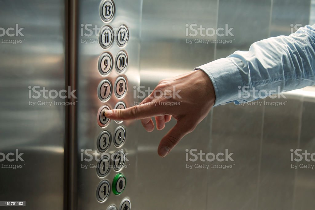 Pressing the button in the elevator stock photo