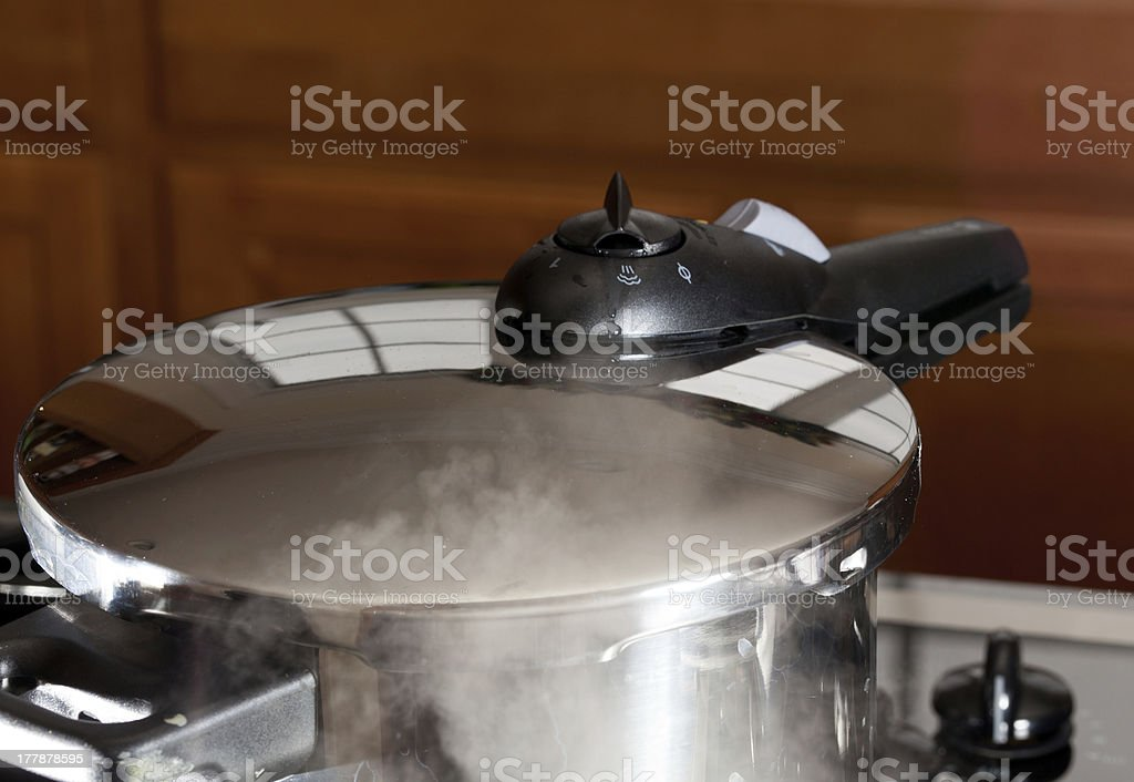Pressure being released from cooker on hob stock photo