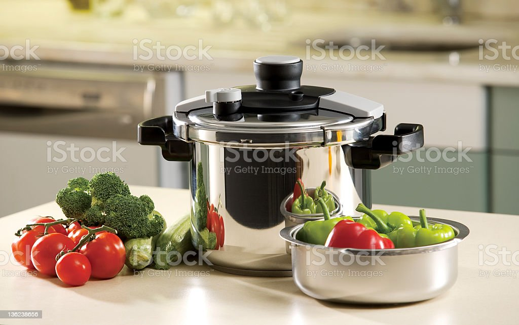 Pressure cooker on a counter with fresh vegetables stock photo