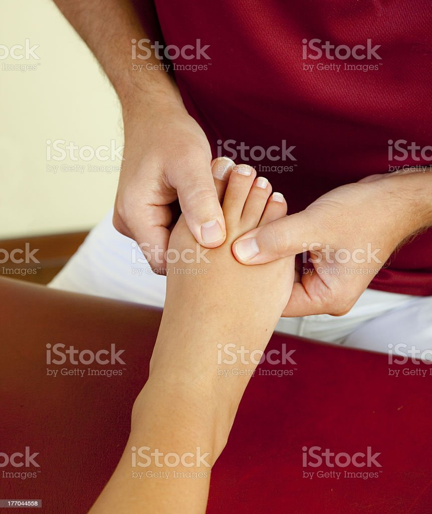 pressure point reflexology massage of female foot and toe royalty-free stock photo