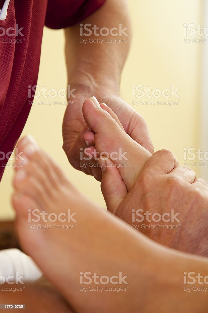 pressure point reflexology massage of foot and toe stock photo