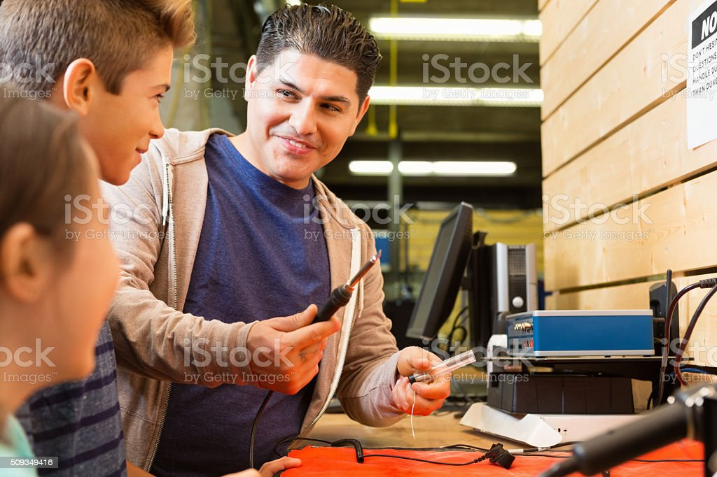 Preteen boy and his sister learn to solder in workshop stock photo