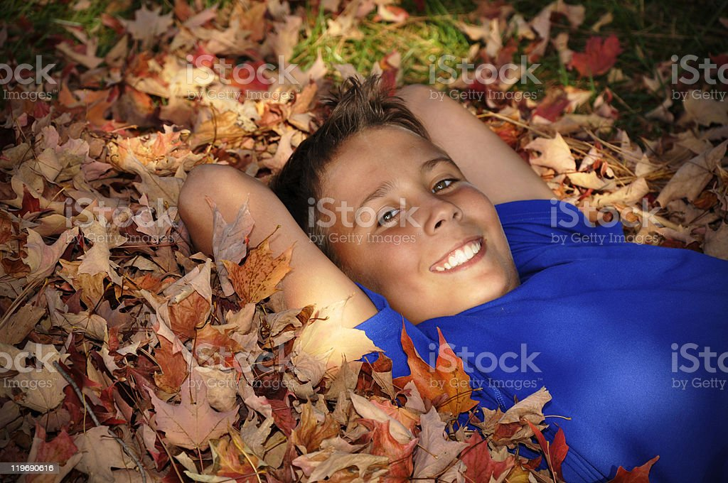 preteen boy laying in autumn leaves royalty-free stock photo