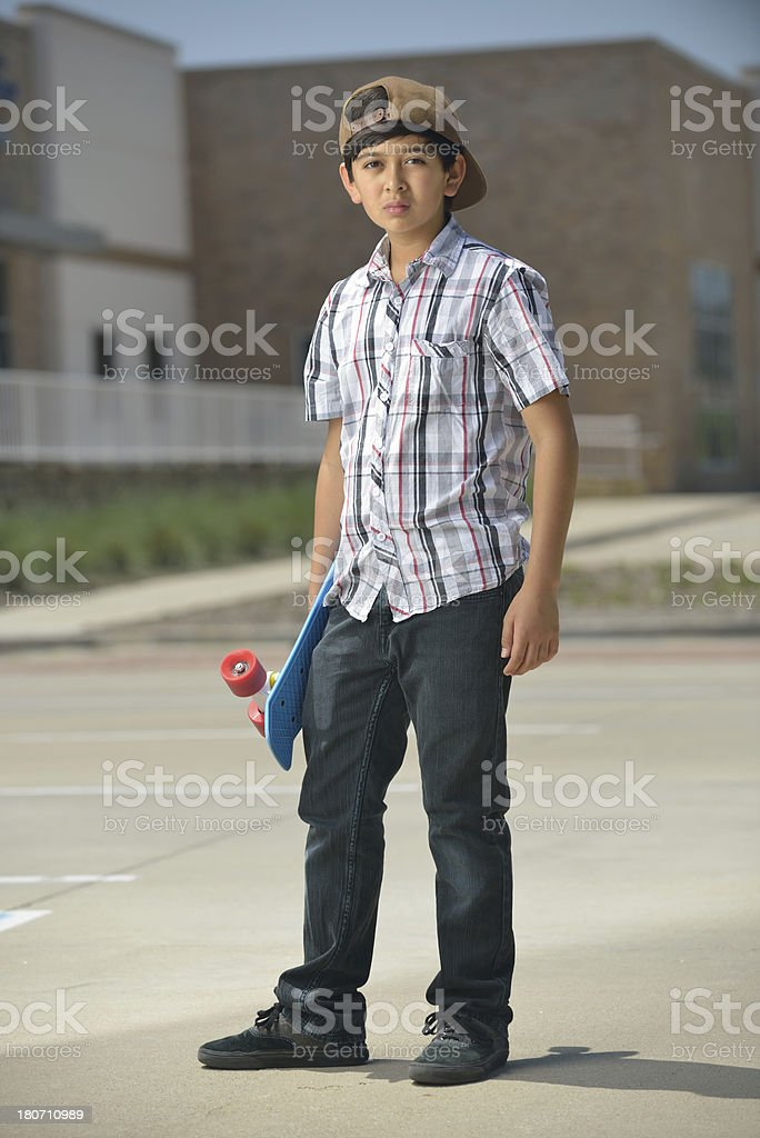 Preteen  boy standing up with his skating board royalty-free stock photo
