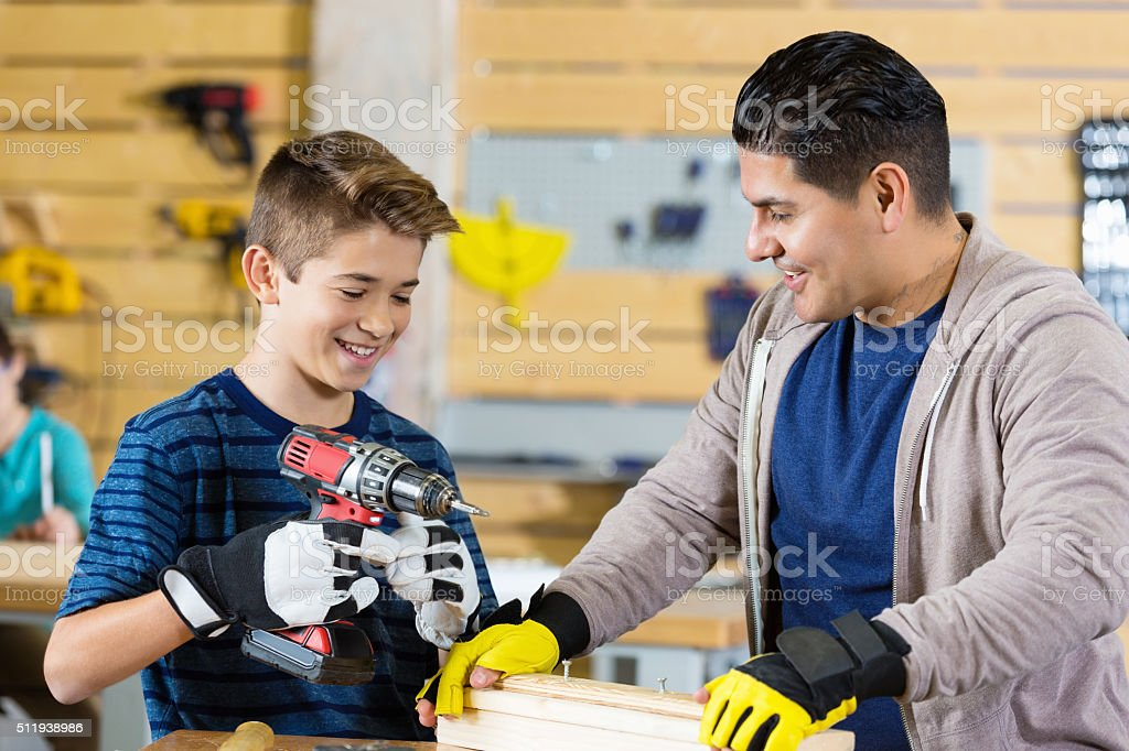 Preteen boy uses power drill in workshop stock photo