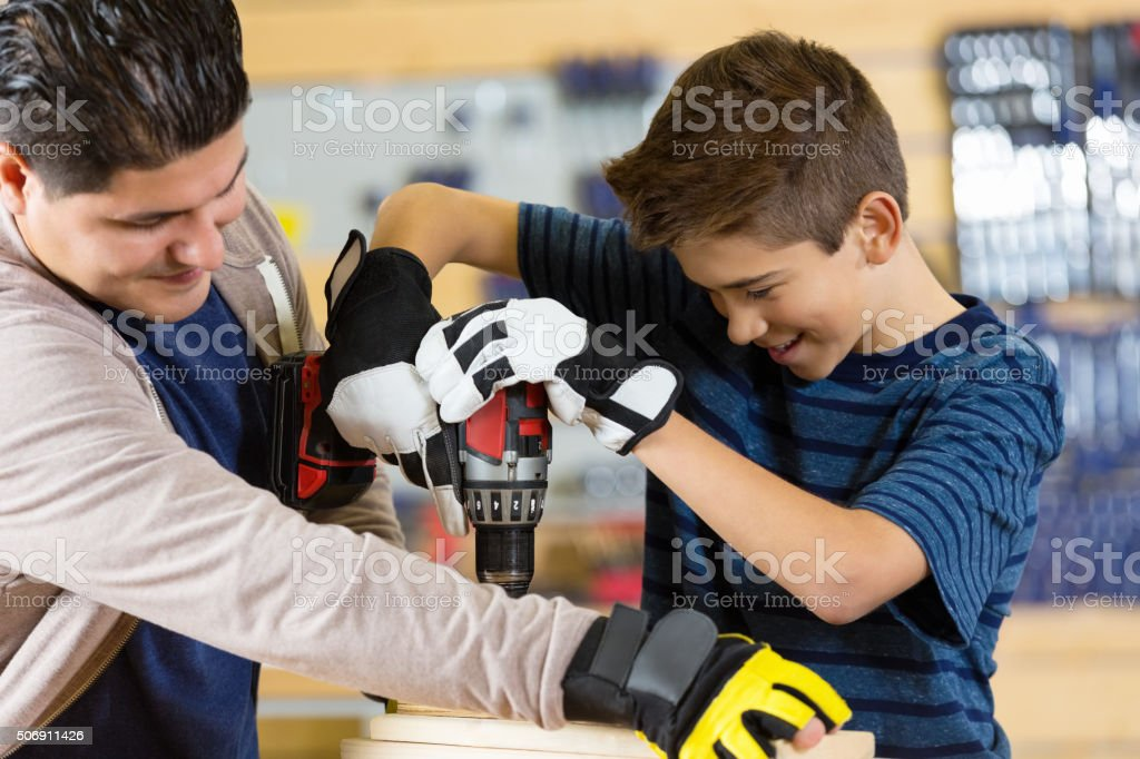 Preteen boy using power tools while building something with dad stock photo