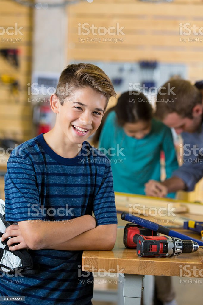 Preteen boy using tools, building something with dad and sister stock photo