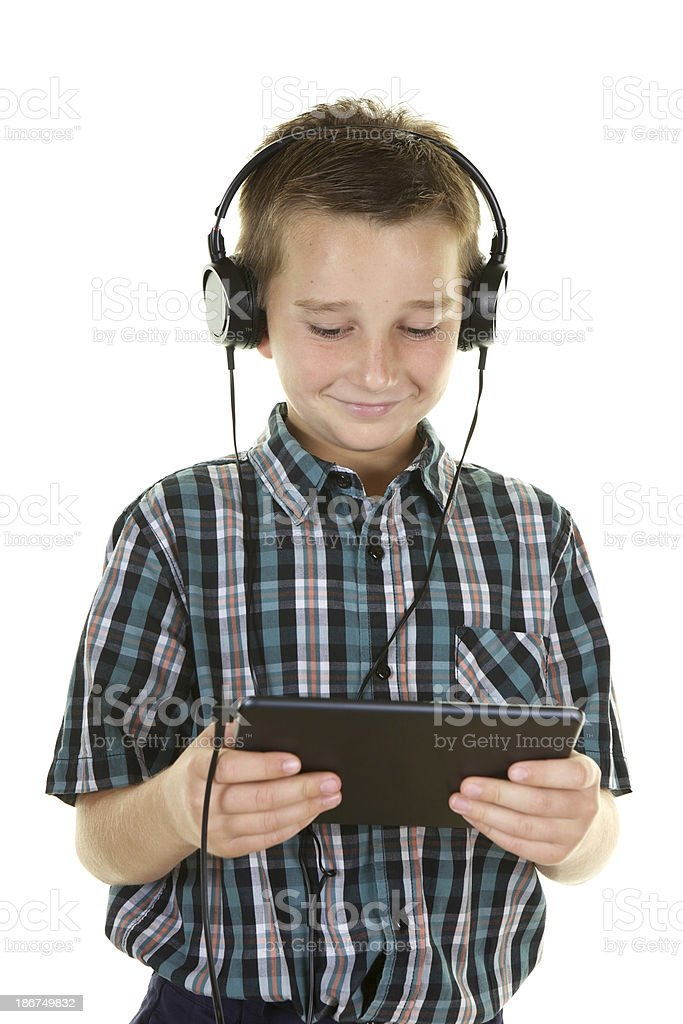 Preteen Boy with Digital Tablet and Headphones on White Background royalty-free stock photo