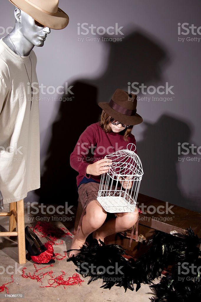 Pre-teen exploring Mannequin, trunk and birdcage in attic. royalty-free stock photo