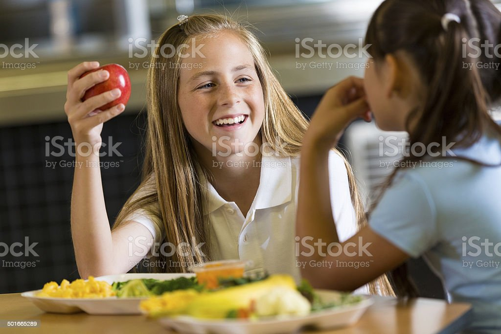 Preteen girl eating healthy lunch with friend in school cafeteria stock photo