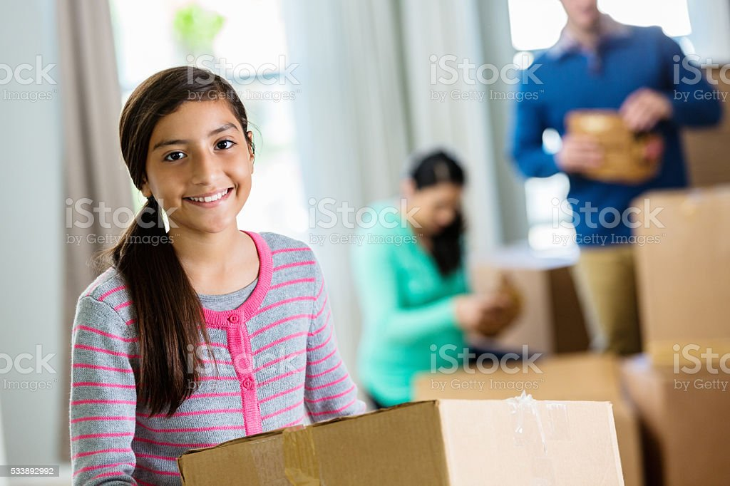 Pre-teen girl holds box in new home stock photo