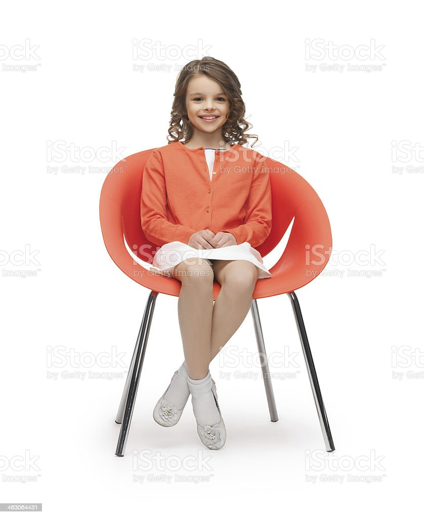 pre-teen girl in casual clothes sitting on chair stock photo