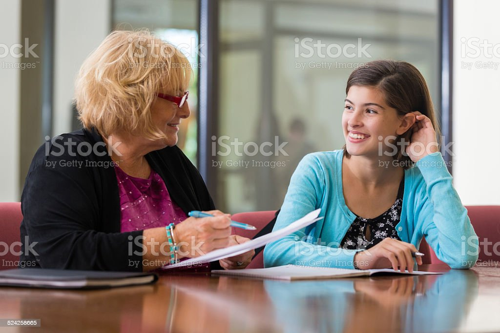 Preteen girl meeting with school counselor or therapist stock photo