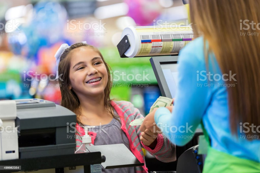 Preteen girl paying for purchase at grocery store stock photo