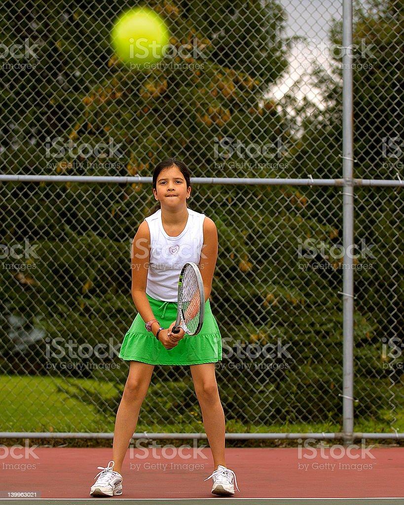 Preteen girl playing tennis royalty-free stock photo