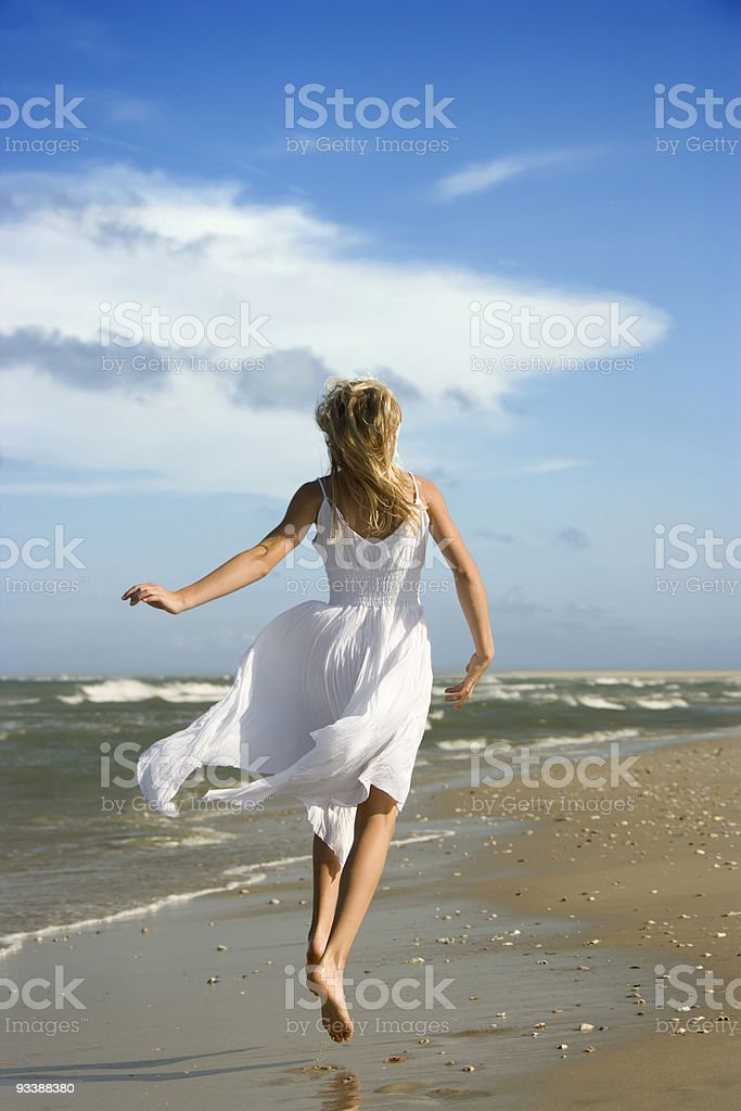 Pre-teen girl running down the beach. stock photo