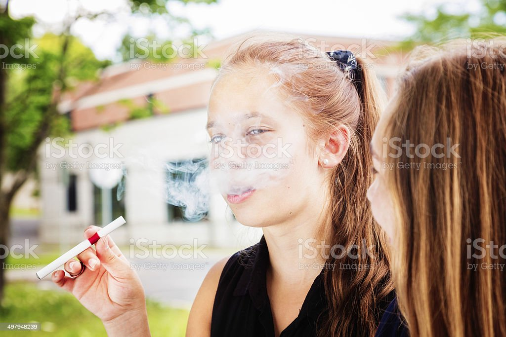 Preteen girl tries e-cigarette with her friend stock photo