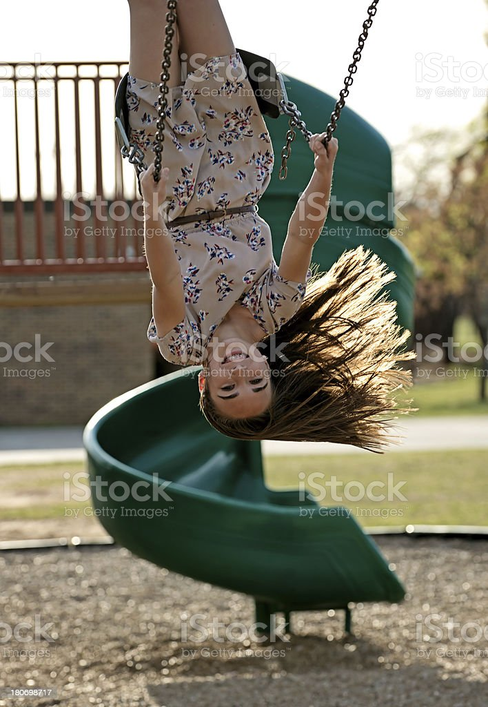 Pre-teen girl upside down on swing royalty-free stock photo
