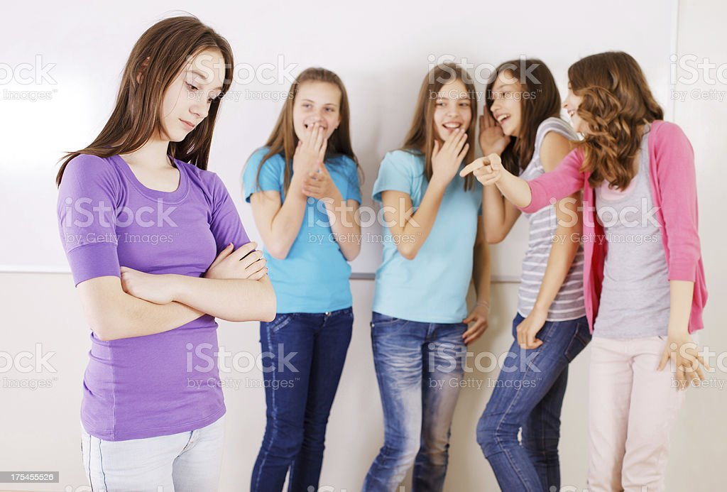 Preteen girls are gossiping their school friend in the classroom royalty-free stock photo