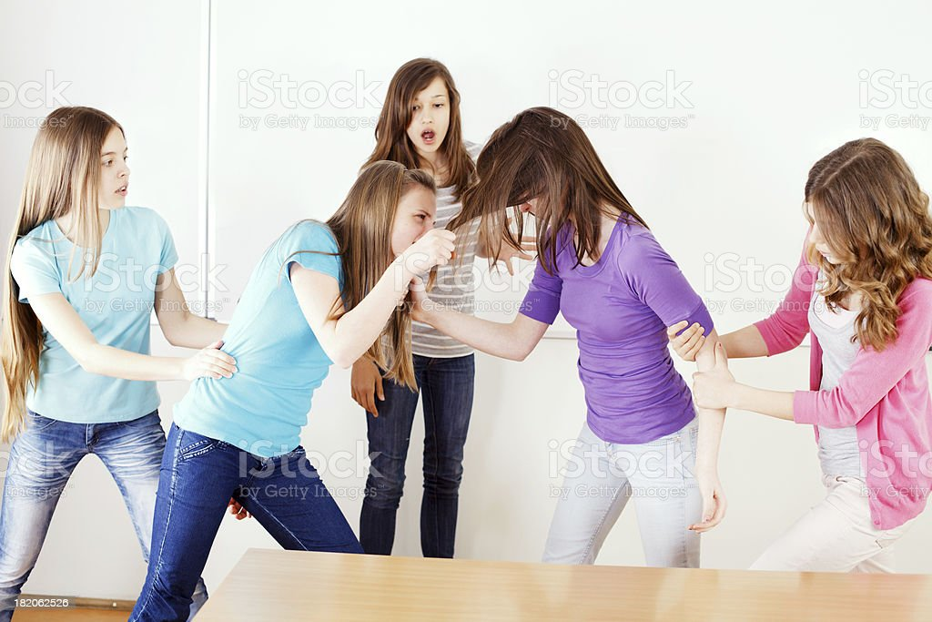 Preteen girls fighting in the classroom royalty-free stock photo