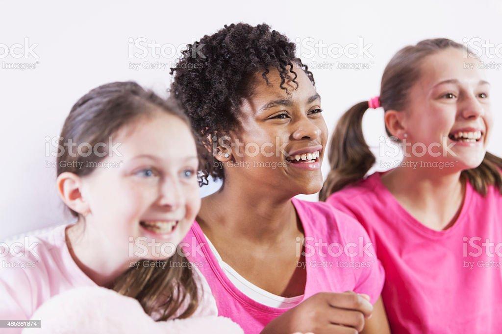 Preteen girls having sleepover, wearing pajamas stock photo
